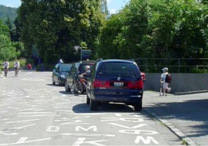 Elterntaxis warten vor dem Schulhaus und versperren dabei die Sicht auf die Schulkinder. (Archivbild verkehrsteiner AG)